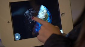 Slow Motion shot of a man that touches a tablet and orbits the model of an Earth. Astronomy exposition.  stock video footage