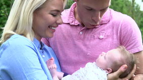 Slow Motion Shot Of Parents Holding Baby Daughter In Garden Royalty Free Stock Images