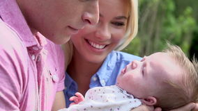 Slow Motion Shot Of Parents Holding Baby Daughter In Garden Stock Photography