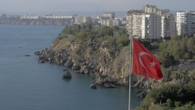 Antalya coast and Turkish flag. Slow motion shot of sea and rocky coast of Antalya with multistorey houses and hotels alongside, fluttering Turkish flag in stock footage