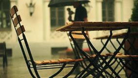 Slow motion shot of street cafe wooden tables and man with umbrella in the rain stock video