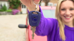 Slow Motion Shot Of Teenage Girl Standing By Car With Key. Happy teenage girl holds out key to car in slow motion sequence.Shot on Sony FS700 in PAL format at a stock video footage