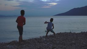 Two Boys Skipping Stones At Sea At Sunset. Slow Motion Shot Of Two Boys On A Pebble Beach Skipping Stones At Sunset stock video footage
