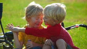 Slow Motion shot of two little boys cyclers sit on a lawn and give five to each other. Success concept. Friendship. Concept stock footage