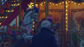 Elder man watching vintage carousel horses stock video footage
