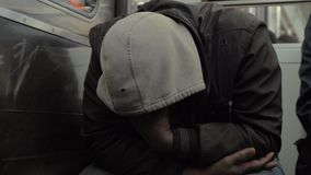 Homeless man dozing when traveling by metro train. Slow motion shot of unidentified homeless man in shabby clothes dozing during subway ride. He sitting with stock video footage