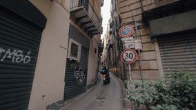 Motorbike in the alleyway of Palermo, Italy. Slow motion shot of unidentified motorcyclist driving through the narrow alleyway in Palermo, Italy stock video