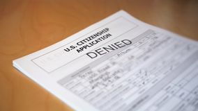 US Immigration citizenship application is denied. A slow motion shot of a United States immigration citizenship application being denied. Fictitious information stock video