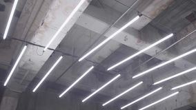 Flickering of Fluorescent Light. Slow motion shot of white fluorescent lighting turn on and off in the dark in industrial building. Many lighting neon lights stock video footage