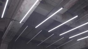Flickering of Fluorescent Light. Slow motion shot of white fluorescent lighting turn on and off in the dark in industrial building. Many lighting neon lights stock footage