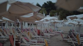 Empty chaise-longues on resort in cloudy windy evening. Slow motion shot of a wind shaking sun umbrellas at the beach with many empty chaise-longues stock footage