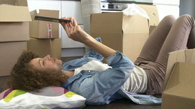 Slow Motion Shot Of Woman With Digital Tablet In New Home. Slow motion sequence of woman lying on the floor amongst moving boxes using digital tablet.Shot on stock video footage