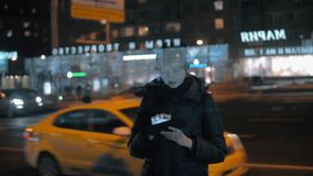 Woman with digital tablet in night city. Slow motion shot of a woman in evening city using touch pad on the background of road with car traffic, view through the stock video footage