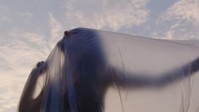 Woman trying to break free from her plastic surrounding. Slow motion shot of a woman trying to break free from her plastic surrounding outdoors at sunset stock video