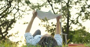 Young attractive asian woman reading book lying down on green grass in the park at sunset. stock footage
