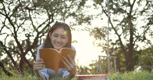 Young attractive asian woman reading book lying down on green grass in the park at sunset. stock video