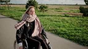 Smiling handicapped woman in wheelchair on enjoyable outdoor walk