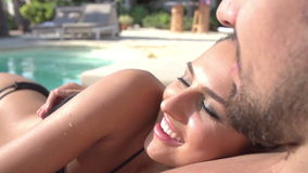 Slow Motion Shot Of Young Couple Relaxing By Swimming Pool stock video footage