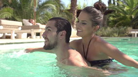 Slow Motion Shot Of Young Couple Relaxing In Swimming Pool stock video