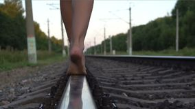 Young girl walking barefoot along railroad rail. Slow motion shot of young girl`s bare feet close-up walking along railroad rail at summer evening stock footage