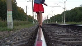 Teenager girl walking barefoot along railroad rail. Slow motion shot of young girl walking barefoot along railroad rail at summer evening stock footage
