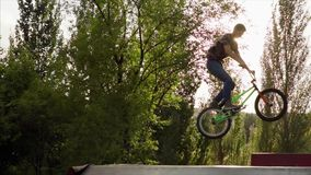 Slow motion shot of the young man performing tricks on the BMX bike. stock footage