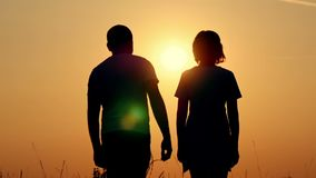 Slow motion silhouette of a happy couple. A guy is hugging a girl against the sunset. Loving man and woman. Slow motin stock video