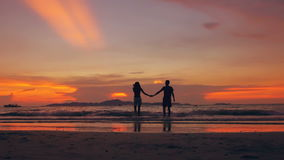 Slow motion silhouette of happy loving couple kiss and go to beach on sunset in ocean shore. Slow motion silhouette of happy loving couple kiss and play at the stock video footage