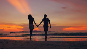 Slow motion silhouette of happy loving couple meet and go to beach on sunset in ocean shore stock video