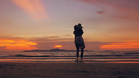 Slow motion silhouette of happy loving couple meet and play at the beach on sunset in ocean shore. Slow motion silhouette of happy loving couple meet and play at stock video