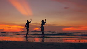 Slow motion silhouette of happy loving couple meet and play at the beach on sunset in ocean shore. Slow motion silhouette of happy loving couple meet and play at stock video footage