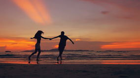 Slow motion silhouette of happy loving couple meet and play at the beach on sunset in ocean shore stock video footage