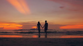 Slow motion silhouette of happy loving couple walk at beach on sunset in ocean shore. Slow motion silhouette of happy loving couple walk at beach and play at the stock video