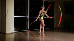 Slow motion, slim cute attractive girl athlete in bright colorful swimsuit performs elements of rhythmic gymnastics with ribbon. In gym on background dark stock video