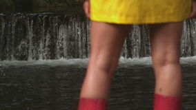 Slow motion of small cascade. Behind womans legs stock video footage