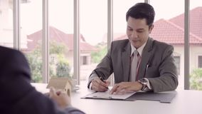 Slow motion - Smart handsome Businessmen signing a house contract, recruitment and agreement with agency concept. Male making a deal stock footage