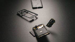 SLOW MOTION: Smartphone falls on a floor, breaks and a parts fly away