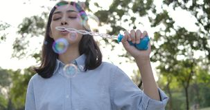 Slow motion of smiles young beautiful asian woman blowing bubble at sunset in the park. stock video footage