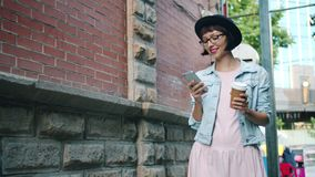 Slow motion of smiling girl using smartphone holding drink walking outdoors. Slow motion of smiling pretty girl using smartphone holding take out drink walking stock footage