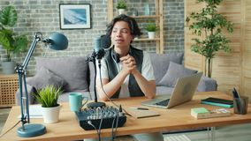 Slow motion of teenage blogger recording podcast audio in microphone at home. Slow motion of smiling teenage blogger recording podcast audio in microphone stock video footage