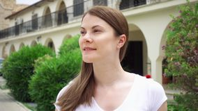 Slow Motion. Smiling young woman in white t-shirt walk down street in european city. Looking around stock video