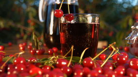 Cherry juice on the background of growing cherries. Slow motion. The smooth glide of the camera  from right to left  along the table with a cherries and juice stock video