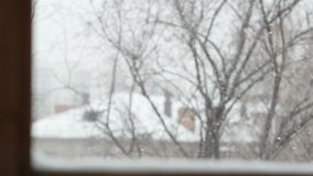 SLOW MOTION: Snowflakes fly in winter - view from window stock video footage