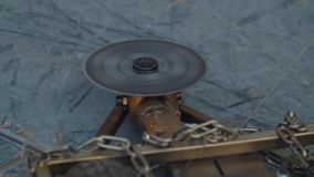 Slow motion spinning circle saw as weapon on battle robot on ring. Slow motion spinning circle saw as weapon on golden metal battle robot covered in chains on stock video