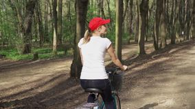 Slow Motion. Woman riding bike. Female teenager biking cycling in sunny park. Active sports concept. Slow Motion. Sportive woman in red cap and white t-shirt stock video footage