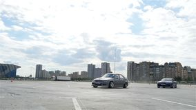 Slow Motion Sports Cars Race and Show Tricks against Buildings. KAZAN, TATARSTAN/RUSSIA - OCTOBER 27 2017: Slow motion sports cars race and show tricks against stock footage