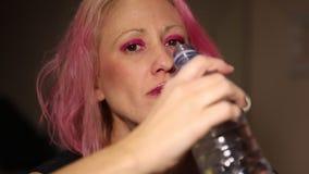 Woman drinking bottle of water stock video footage