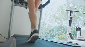 Sporty young woman running on treadmill, close-up rear view. Slow motion of sporty young woman running on treadmill. Close-up of feet and butt, rear view stock video