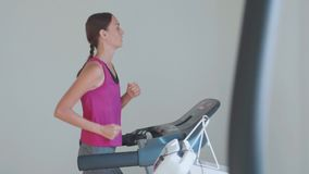 Sporty young woman running on treadmill, close-up rear view. Slow motion of sporty young woman running on treadmill, close-up rear view stock video footage