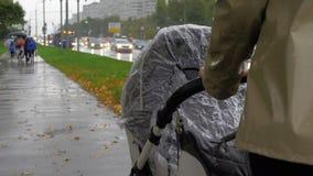 Mum walking with baby on rainy autumn day